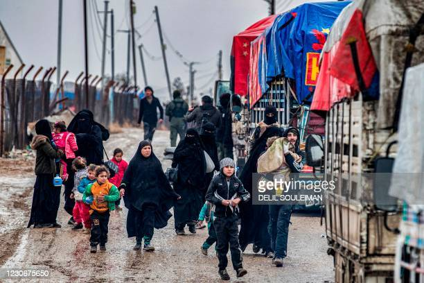 Man carries a child as he walks with other women and children ahead of a member of the Syrian Kurdish internal security services known as Asayish as...