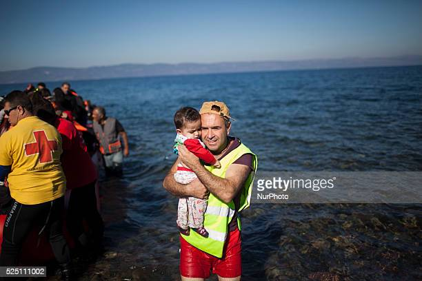 A man carries a child as refugees and migrants get off a dinghy upon their arrival on the Greek island of Lesbos after crossing the Aegean Sea from...