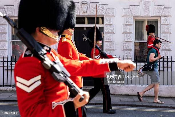 A man carries a child dressed in ceremonial outfit during the changing of the guard outside Windsor Castle as the town continues it's preparations...