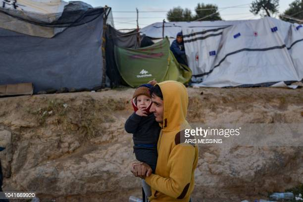 A man carries a child in a camp outside the refugee camp of Moria in the northern Greek island of Lesbos on September 25 2018 Despite a 2016...