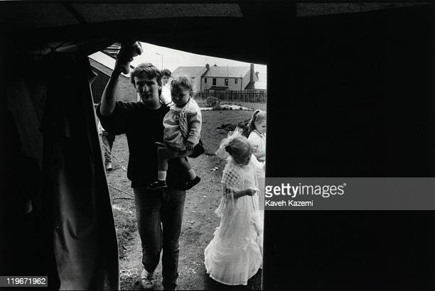 A man carries a child into a tent during children's fair in west Belfast Northern Ireland 9th August 1986