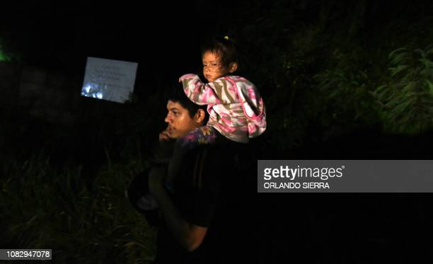 A man carries a child on his shoulders as Honduran migrants part of the second caravan to the United States leave San Pedro Sula 180 km north of...