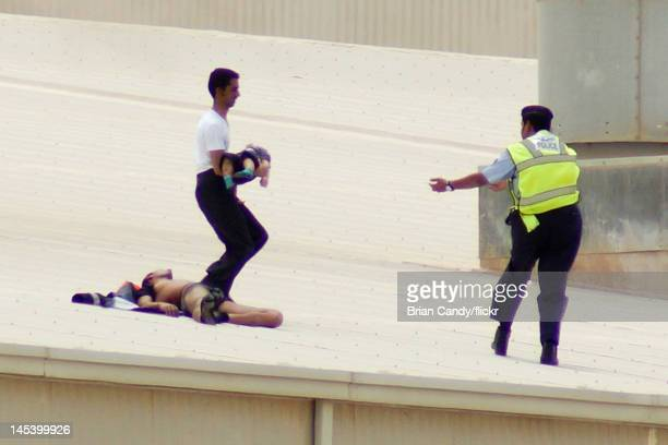 Man carries a child past a man injured in a fire at the Villaggio mall on May 28, 2012 in Doha, Qatar. A fire at the Villaggio mall shopping centre...
