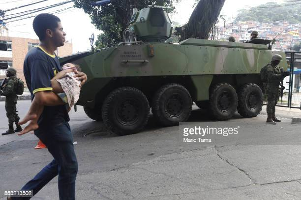 A man carries a child past an armored military vehicle in the Rocinha 'favela' community on September 24 2017 in Rio de Janeiro Brazil The Brazilian...