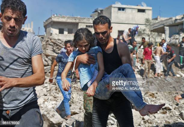 TOPSHOT A man carries a child rescued from rubble after Syrian regime and Russian air strikes in the rebelheld town of Nawa about 30 kilometres north...