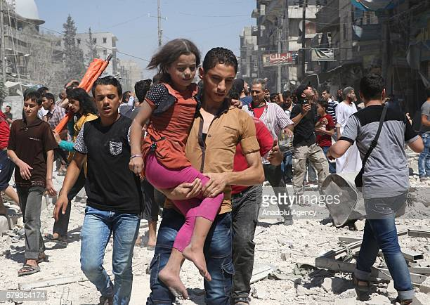 A man carries a child through rubble as civil defense team members and the citizens try to rescue people who were trapped under the wreckage after...