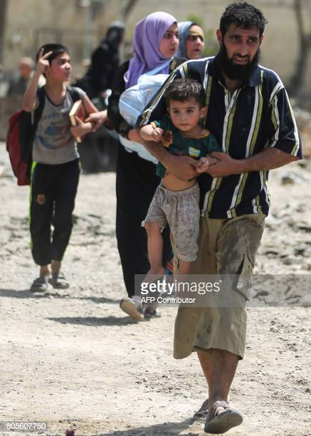 A man carries a child while fleeing from the Old City of Mosul on July 2 as Iraqi government forces continue their offensive to retake the city from...