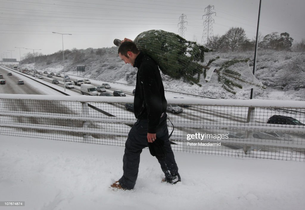 A man carries a Christmas tree through the snow over the M25 motorway on December 18, 2010 near Leatherhead, England. The United Kingdom is continuing to suffer heavy snowfall causing misery for travellers as it was warned there would be severe disruption to all London airports after British Airways cancelled all flights out of Heathrow until 17:00 GMT today and flights out of Gatwick between 10:00 and 16:00GMT.