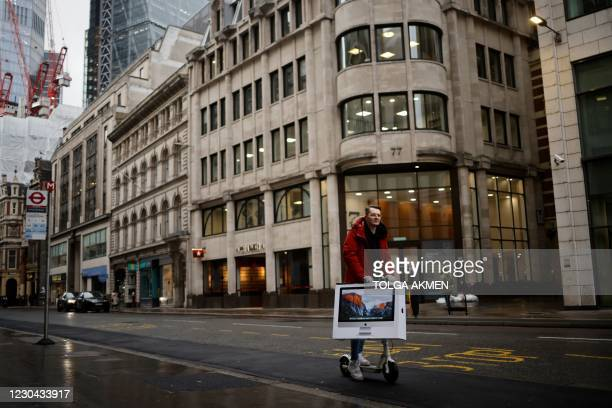Man carries a computer as he rides through the City of London on an e-scooter as Britain enters a national lockdown in London on January 5, 2021. -...