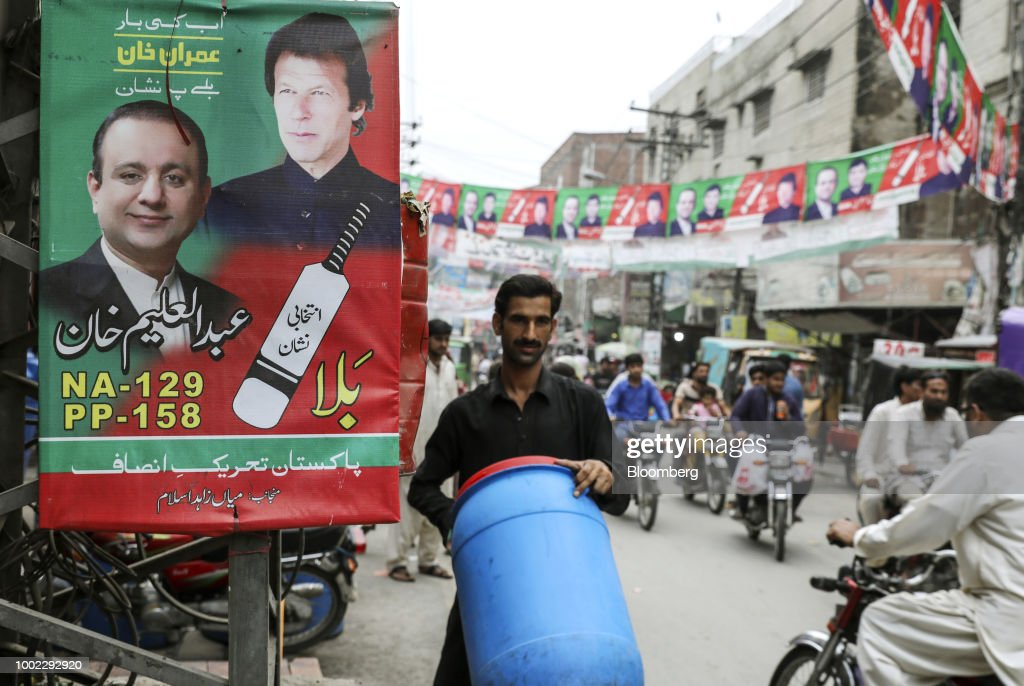 A man carries a container past a campaign poster for Pakistan TehreekeInsaf also known as Movement for Justice in Lahore Pakistan on Thursday July 17.