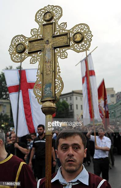 A man carries a cross during a march toward the Holy Trinity Cathedral in Tbilisi on July 9 as they protest against President Mikheil Saakashvili's...