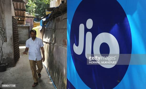 A man carries a cup of as he walks past a Reliance Jio Infocomm 4G mobile services logo in Mumbai on September 6 2016 India's richest man Mukesh...