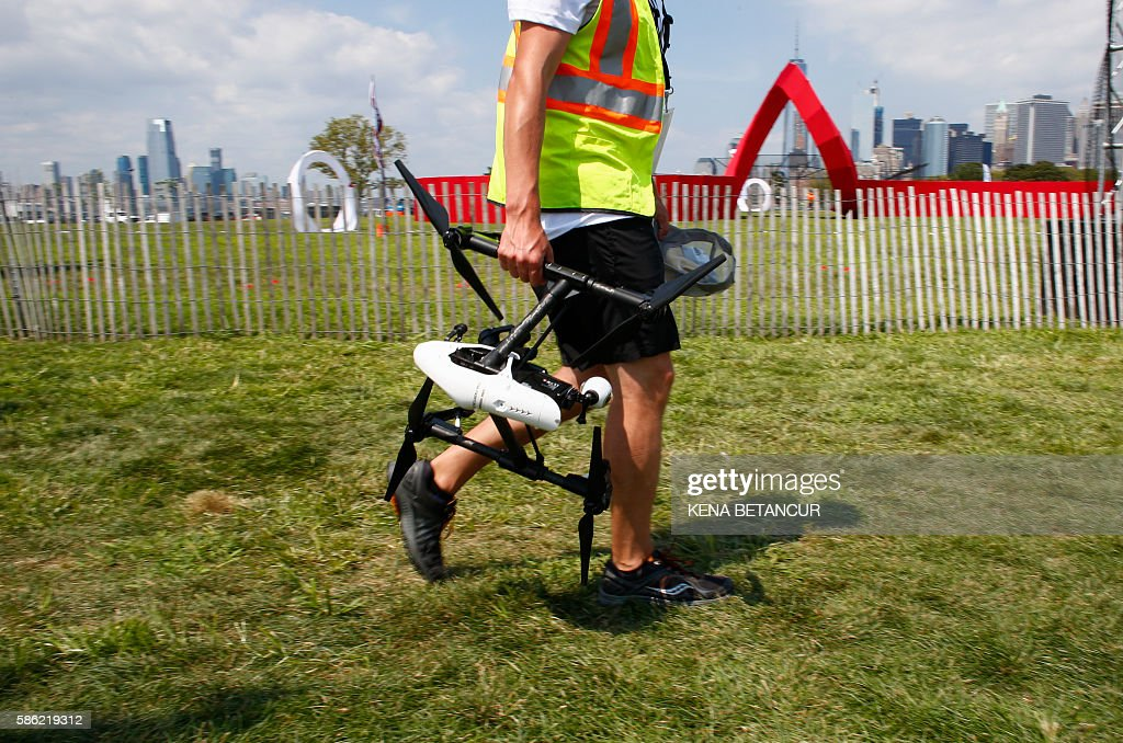 A man carries a drone during the practice event before the National Drone Racing Championship at Governors Island in New York on August 5, 2016. More than 100 pilots are expected to compete. Winners from the Drone Nationals will be selected to represent Team USA. / AFP / KENA