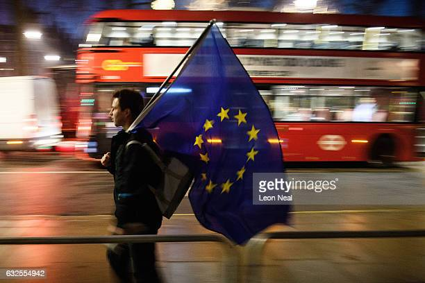A man carries a European Union flag outside the Supreme Court in Parliament Square ahead of the ruling on whether Parliament have the power to begin...