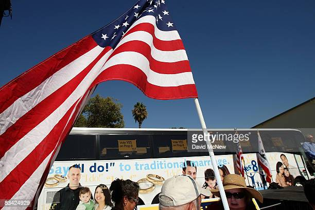 A man carries a flag as supporters of Proposition 8 which would outlaw samesex marriage throughout California rally during a 'Yes on 8 bus tour' stop...