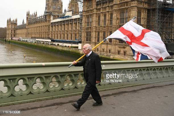TOPSHOT A man carries a flag of St George the English national flag along with a Union Flag as he walks along Westminster Bridge by the Houses of...