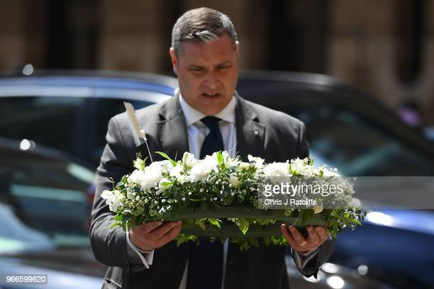 A man carries a floral tribute from Cressida Dick Commissioner of the Metropolitan Police Service as he arrives at Southwark Cathedral to attend the...