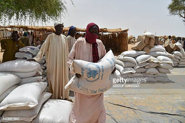 A man carries a food bag as displaced people fleeing from Boko Haram incursions into Niger attend a World Food Programme and USAID food distribution...