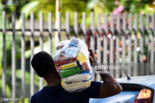 Man carries a food package on March 31, 2020 in Belo Horizonte, Brazil. Belo Horizonte city council started to distribute food packages to families...