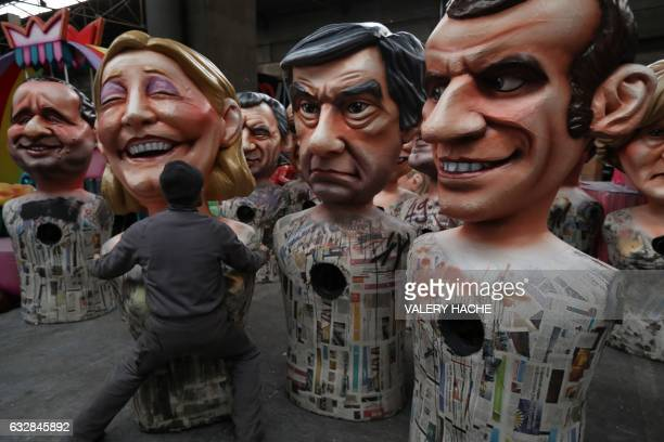 A man carries a giant figure depicting far right presidential candidate Marine Le Pen next to others depicting presidential candidates Francois...