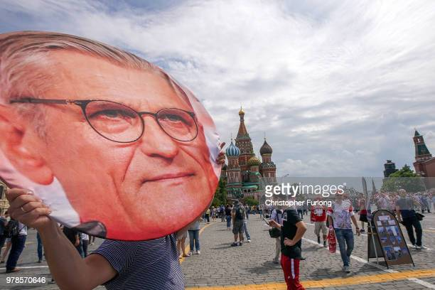 A man carries a giant picture of Poland's manager Adam Nawalka as Polish football fans gather in Red Square and sing before their World Cup game...