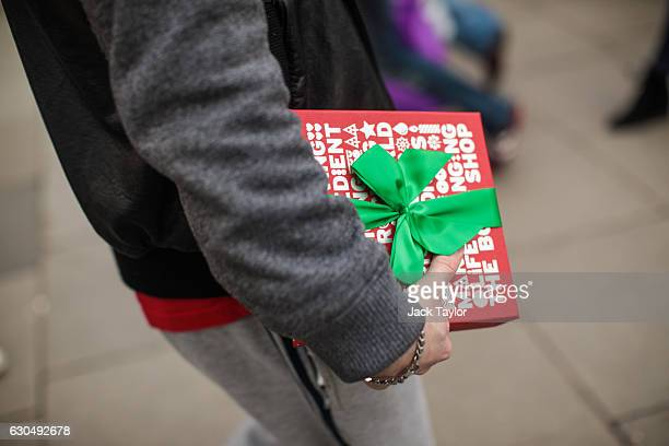 Man carries a gift-wrapped box on Oxford Street on December 24, 2016 in London, England. Christmas shoppers hunt for last minute presents in central...