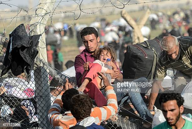 A man carries a girl as Syrians fleeing the war pass through broken down border fences to enter Turkish territory illegally near the Turkish Akcakale...
