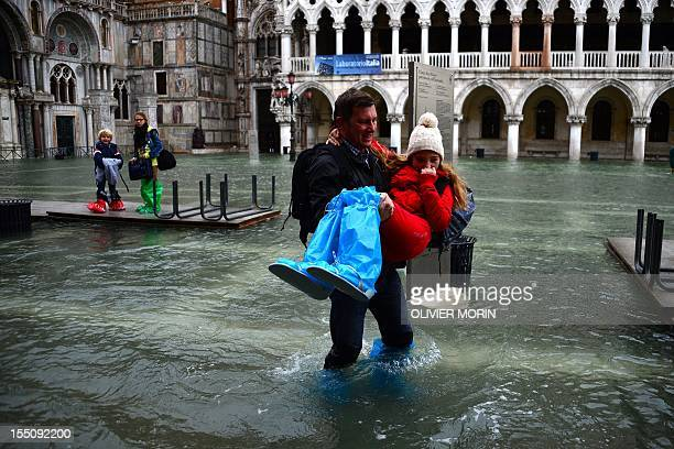 A man carries a girl as they leave the flooded St Mark's square during acqua alta on November 1 2012 in Venice Floodwaters drenched Venice's St...