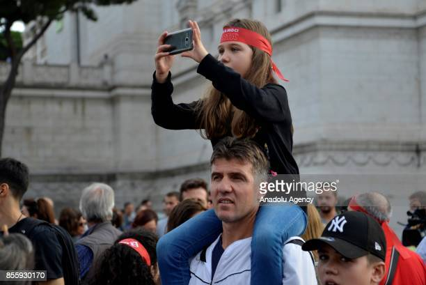 A man carries a girl over his shoulders during a protest against genderbased violence in Rome Italy on September 30 2017