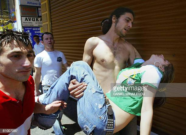A man carries a girl who fainted due to the inhalation of tear gas used by Turkish police during a protest against the NATO meeting on Istiklal...