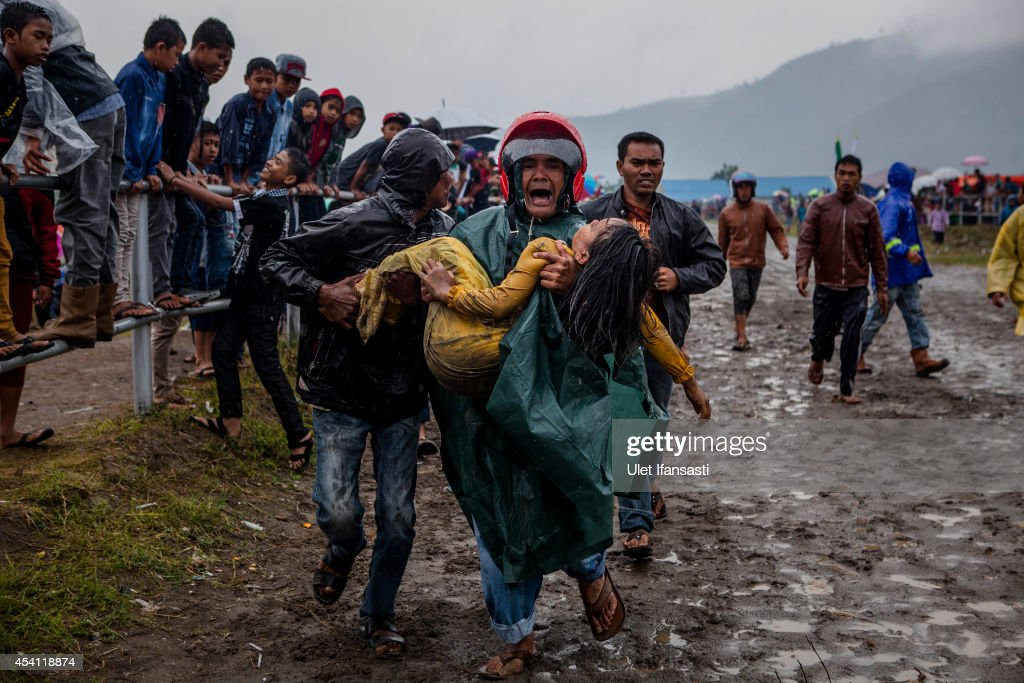 A man carries a girl who was struck by a horse during the Takengon traditional horse races on August 23, 2014 in Takengon District, Central Aceh, Sumatra Island, Indonesia. The races, which began in colonial times and originally took place on the banks of Lake Lut Tawar in Bintang district in the late 1930s, now commemorate Indonesian independence. The 12-year-old jockeys ride bareback.