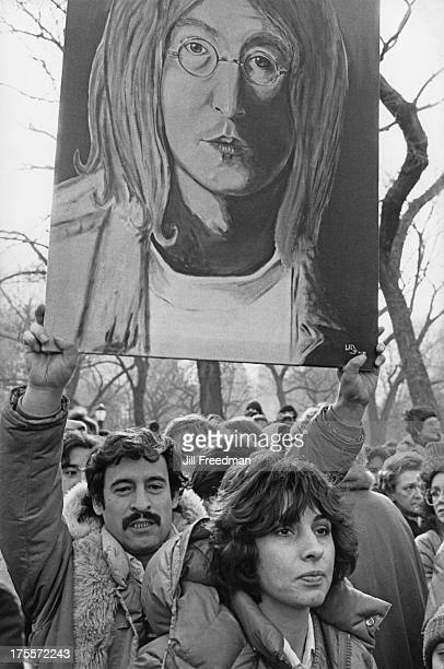 A man carries a hand painted picture of John Lennon as people gather in Central Park to mourn his death New York City 1980