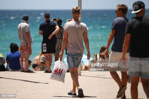 A man carries a Hennes Mauritz AB shopping bag at Manly Beach in Sydney Australia on Friday Jan 5 2018 The Australian Bureau of Statistics is...