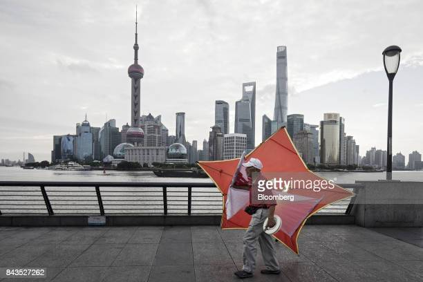 A man carries a kite along the bund as the Lujiazui Financial District stands in the background in Shanghai China on Monday Sept 4 2017 The Chinese...