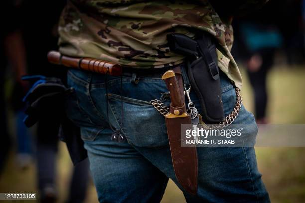 Man carries a knife and a handgun as several hundred members of the Proud Boys and other similar groups gathered for a rally at Delta Park in...