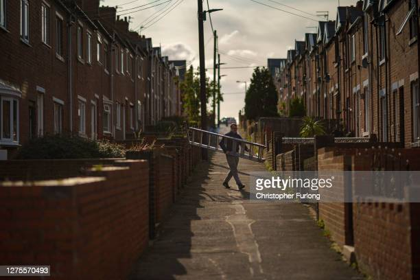 Man carries a ladder through the quiet streets on September 18, 2020 in Easington Colliery, United Kingdom. Since easing its first nationwide...