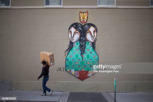 Man carries a large box past a Juarez/El Paso sister-city mural near the Paso del Norte International Bridge, Friday, February 3 in El Paso, Texas....