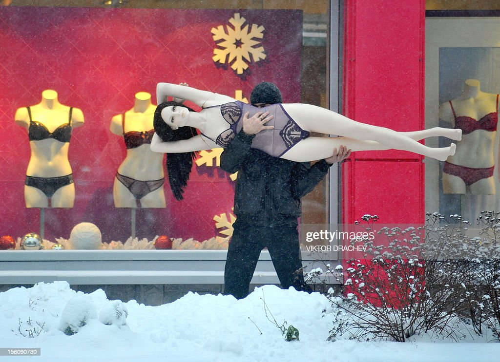 A man carries a mannequin in the Belarus capital Minsk, on December 10, 2012.