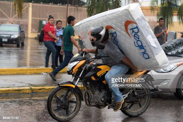 TOPSHOT A man carries a matress looted from a shop as supporters of Honduran presidential candidate for the Opposition Alliance against the...