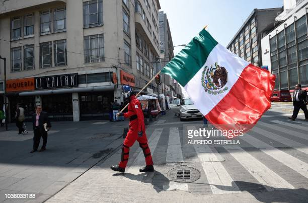 A man carries a Mexican flag in the surroundings of the Alameda Central urban park in downtown Mexico City during an earthquake drill on September 19...