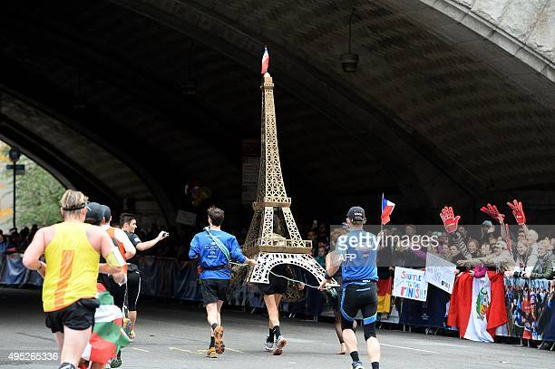 A man carries a model of Eiffel Tower as he runs during the TCS New York City Marathon in New York on November 1 2015 / AFP / JEWEL SAMAD