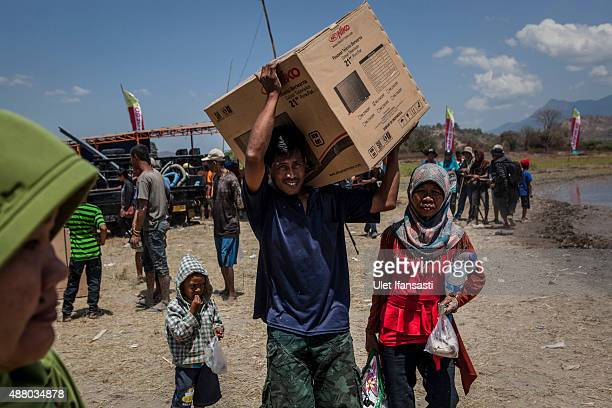 A man carries a new television which he won after his buffalos won the race during the Barapan Kebo or buffalo races as part of the Moyo festival on...
