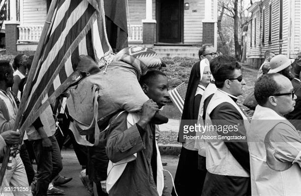 Man carries a pack over his shoulders as he walks with others, including a nun and a man with an eyepatch, during on the Selma to Montgomery marches...