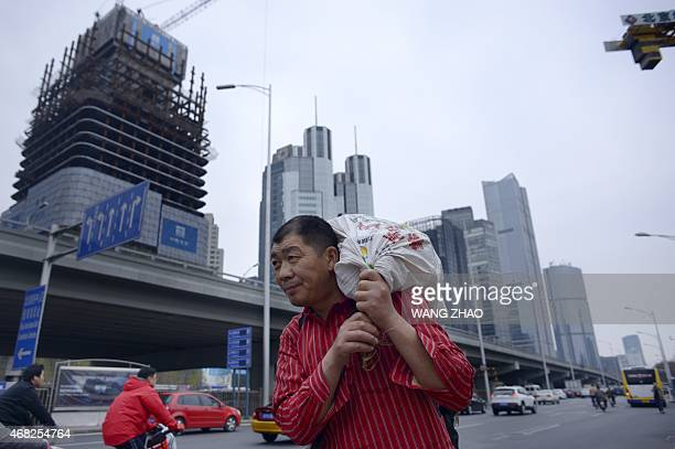 A man carries a package as he walks along a street at a Central Business District in Beijing on April 1 2015 China scored a diplomatic coup by...