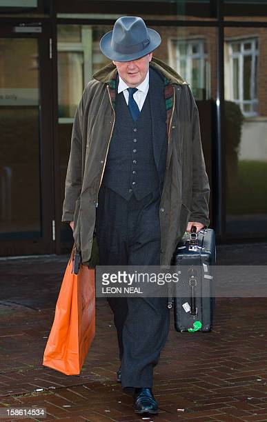 A man carries a painting away from Isleworth Crown Court in Isleworth west London on December 21 2012 after an appearance by actress Koo Stark former...