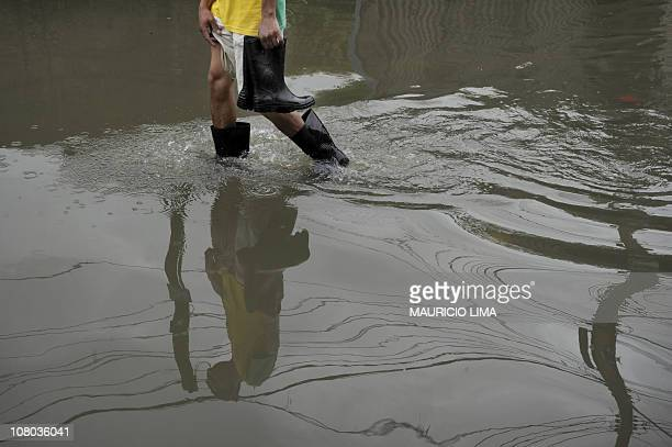 A man carries a pair of rain boots in a flooded area at Jardim Itaim neighbourhood eastern outskirts of Sao Paulo Brazil on January 13 2011 Brazil...