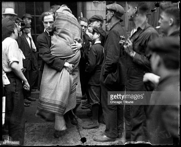 Man carries a person wrapped in blankets after the SS Eastland disaster July 24 in Chicago. Local stores, hotels and restaurants opened their doors...