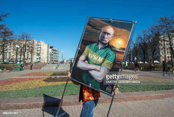 A man carries a picture depicting Russia's President Vladimir Putin in a Tshirt with an inscription reading 'Crimea' at an openair political cartoons...