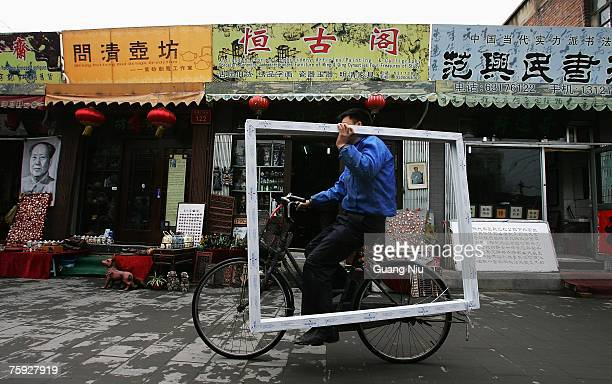 A man carries a picture frame as he rides his bicycle through a street selling traditional Chinese paintings and calligraphy scrolls on April 12 2007...