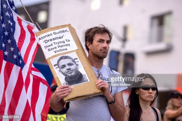 A man carries a picture of Alonso Guillen as thousands of immigrants and supporters join the Defend DACA March to oppose the President Trump order to...